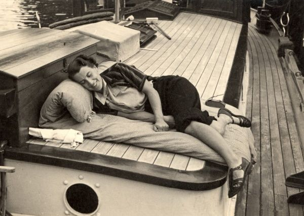 A woman takes a well earned rest on board a boat after recovering the cabin roof in teak!
