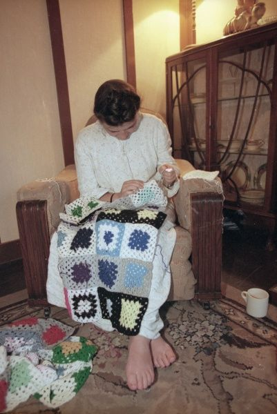 A young woman sitting in her armchair sews together crocheted squares, today's equivalent of knitting blankets for the troops during World War Two