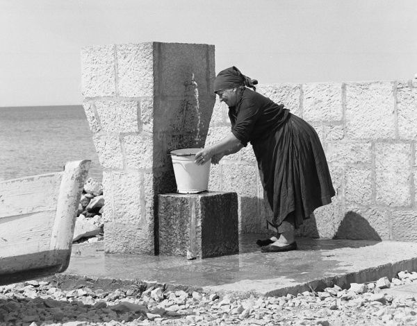 A middle aged woman filling a bucket with water from an outdoor tap near the sea. She is wearing dark clothes and a headscarf