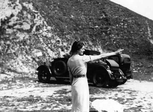 A woman fires a revolver. Let's hope she's not unhinged. Date: 1930s
