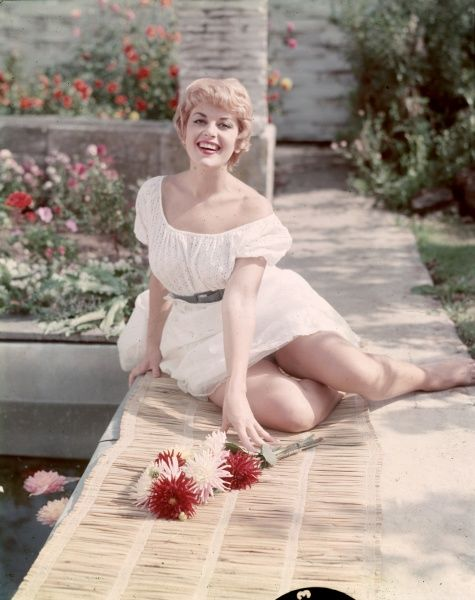 Smiling blonde, wearing a white, peasant style dress, sits on a rush mat on a path in a sunny garden