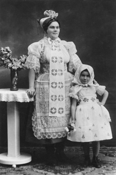 A woman and a little girl wearing traditional East European folk costume, probably from Moravia or Slovakia