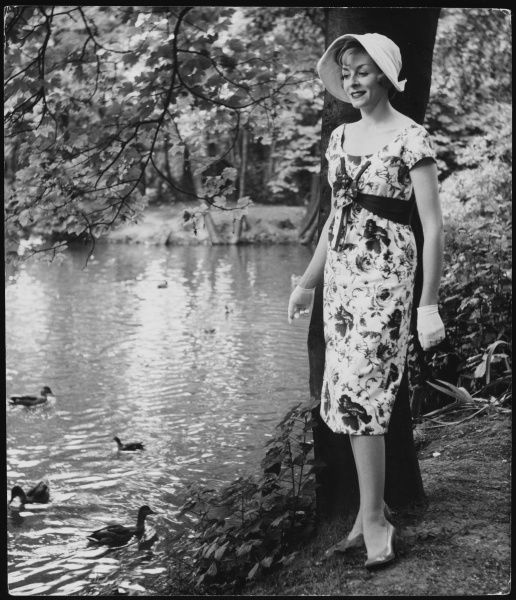 A woman poses by a lake, formally dressed with hat & gloves