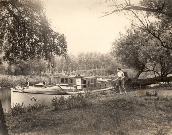 Picturesque scene showing a woman using a boat hook to moor a boat on the Norfolk Broads in East Anglia during the 1930s