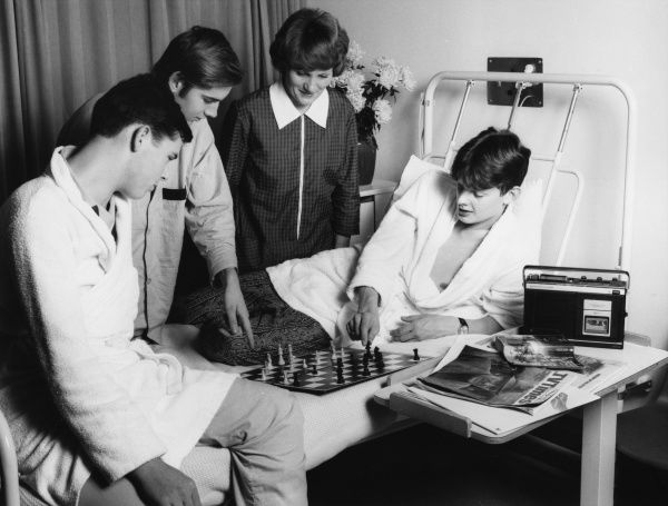 Scene at the Metropolitan Police Medical Centre, Hendon, north west London, showing a woman in overalls discussing a game of chess with three patients in a hospital ward