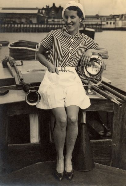 A woman sits between a shiny brass horn and a polished rear view mirror wearing a chic outfit of shorts, striped blouse, white cap and court shoes on the deck of her boat at Rochester in Kent