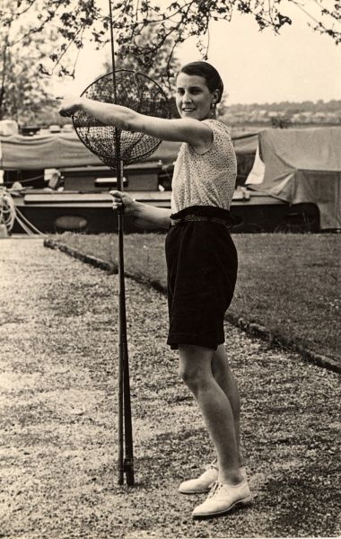 A woman in sassy shorts, sleeveless blouse and fashionably cropped hair poses with fishing net and rod at Beccles on the Norfolk Broads in East Anglia in the 1930s