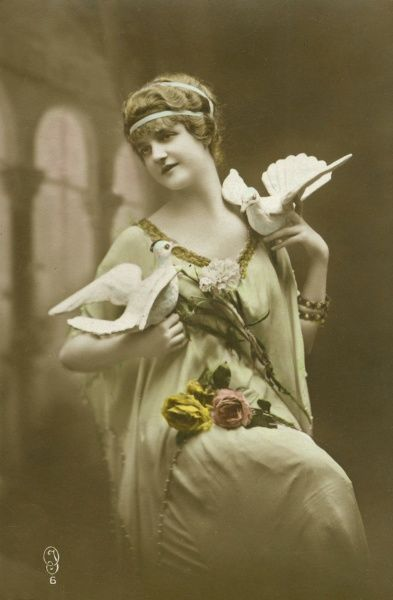 A woman in a pale green dress, posing with two plaster doves and some roses in her lap. She has a matching pale green ribbon in her hair, tied in Greek style. Date: early 20th century