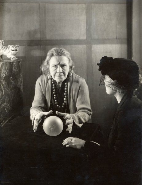 A woman concentrates on her crystal ball which she is reading for a younger woman who is wearing a black hat with a veil
