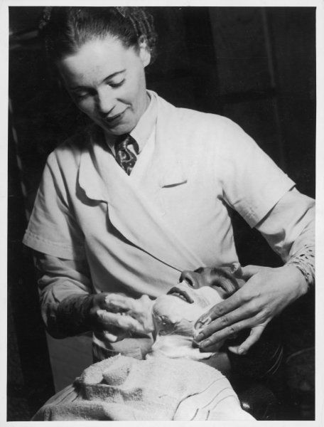 A female barber or barber's assisitant, probably during World War Two, applies shaving soap to a man's face before his shave