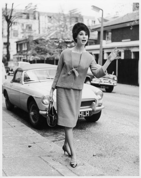 A woman in smart stylish suit of straight knee-length skirt & a collarless sac like short jacket with tie fastening, fur hat & stiletto heels hails a taxi