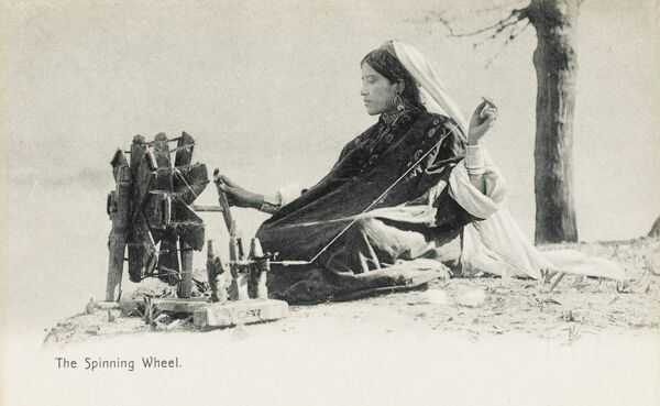 Woman spinning on a traditional hand-made wheel, India