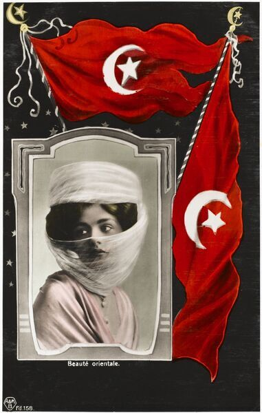 A veiled 'oriental beauty' with pretty eyes set in a frame beneath two Turkish flags - patriotic postcard