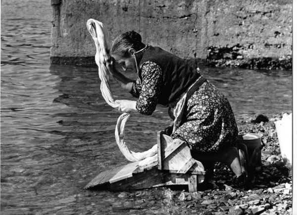 Woman washing a sheet at the side of a river in Portugal. She is kneeling on a specially designed wooden platform, which stops her getting too wet