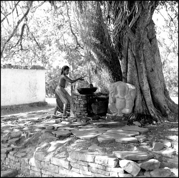 A woman collecting water from a well in an unidentified location in India. Photograph by Ralph Ponsonby Watts