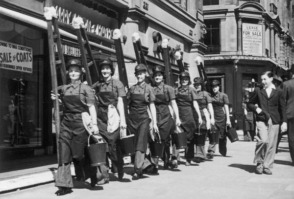"A smart line of newly trained ""Georginas"" march in single file down a central London street, carrying their ladders and buckets and are greatly admired by a dapper young man"