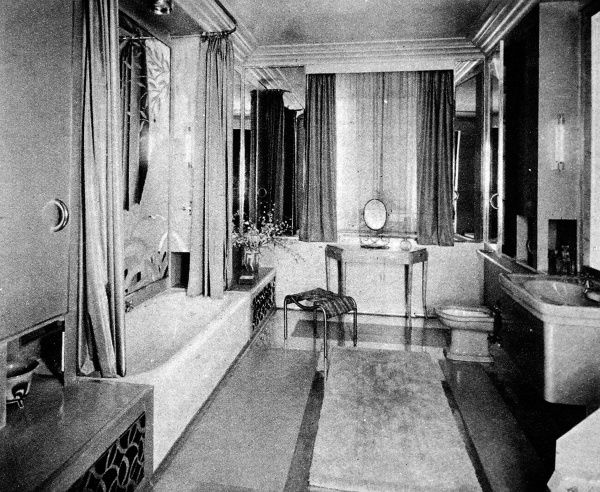 A woman's bathroom; a feminine sheme of delicately engraved mirrors, with maple furniture and radiators under drying cupboards