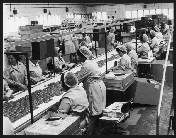 Women working on a conveyor belt in a biscuit factory in the outskirts of London