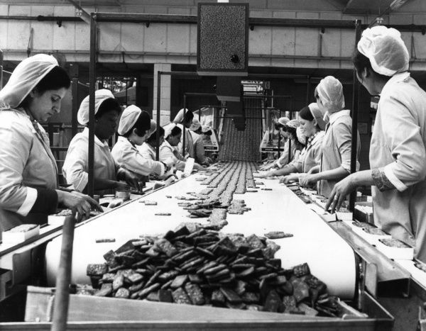 Women working in a biscuit factory on the outskirts of London. Date: 1971