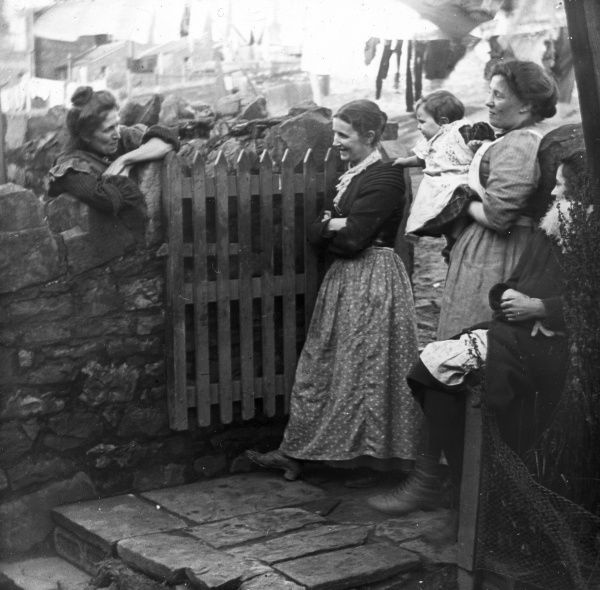 A group of women, probably all wives of coal miners, chatting in the back yard of 76 Hanbury Terrace, Pontypool, South Wales. The smiling woman in the spotted skirt is the mother of W E Jones