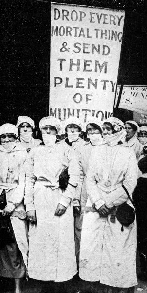 A group of female factory workers wearing respiratory-veils and carrying a banner. The photograph was taken during a procession in London in July 1916 celebrating the many different roles of women in the war effort