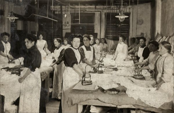 A room full of women ironing what appear to be bed sheets. The location may be an institution such as a workhouse or prison. A supervisor stands right of centre