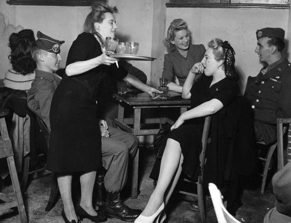 Women and military men enjoying a drink in a pub, while a barmaid collects some empty glasses