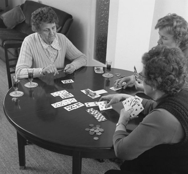 Three middle aged women playing cards at a table. They are playing for money, and there are three half-empty glasses of sherry