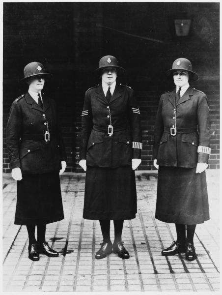 Three female Metropolitan Police officers pose in their uniforms before starting work