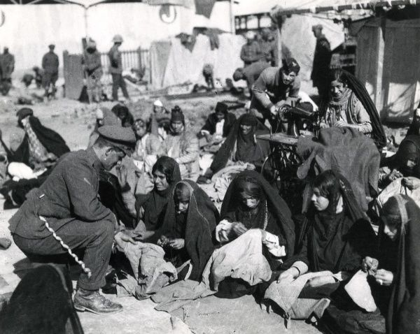 Women refugees sewing army clothing in Baghdad, Mesopotamia (now Iraq) during the First World War. One woman is using a Singer automatic sewing machine. Date: 1917