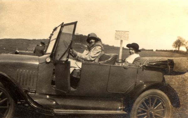 A woman at the wheel of an open-top sports car