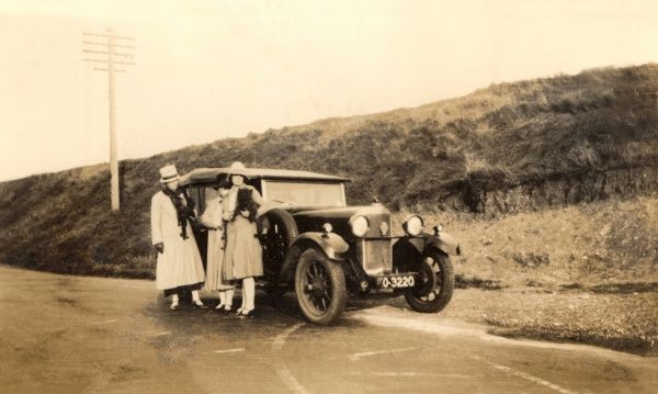 Two women and a young girl (wrapped up well aginst the wet weather) stand next to their large soft top car at the side of a country lane