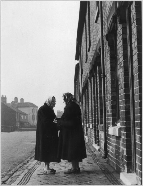 Two elderly women in coats, both wearing headscarves, one in her indoor slippers, exchange news and gossip on the pavement of an otherwise deserted London street