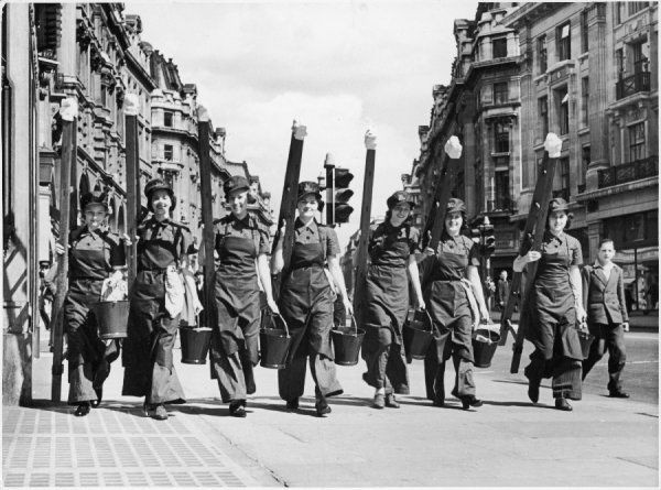 A group of newly trained 'Georginas' set off for their first job, carrying their ladders and buckets. Date: 1940s