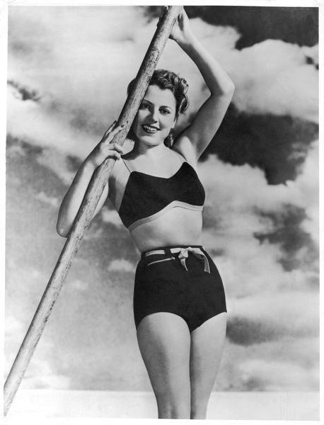A radiant young lady poses against a dramatic sky in her stylish two-piece woollen bathing costume in which she would be advised to continuing posing rather than attempt swimming