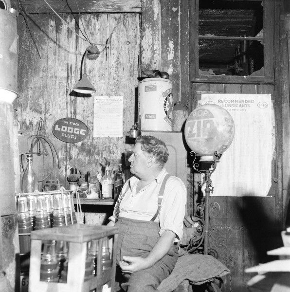 Worcestershire garage and seated owner surrounded by oils, engine treatments and lubricants. Photograph by Norman Synge Waller Budd