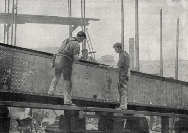 Workers riveting the centre girder of a turret vessel at Messrs Droxford & Sons, a shipyard in Sunderland