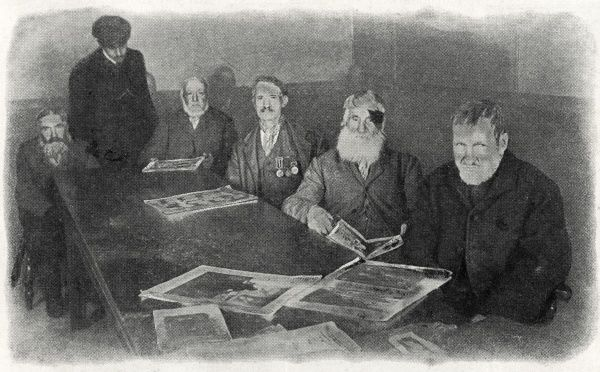 A group of elderly 'workhouse veterans' sit at a table covered with newspapers and magazines. One of the men is wearing a row of medal, another has a patch over one eye. Date: 1909