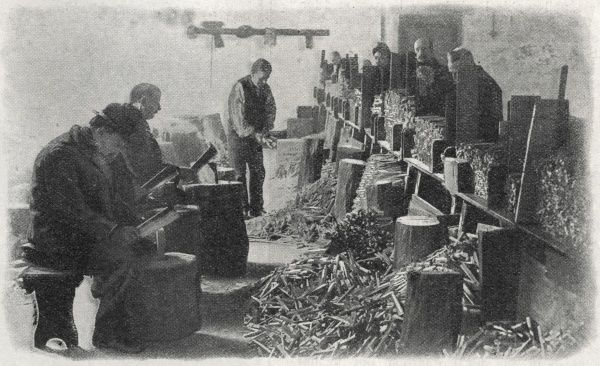 The wood-chopping shed at an unidentified workhouse. Wood-chopping was a work task often given to workhouse inmates. Some of the men area seated with small cleavers. Others are standing and collecting the chopped wood into bundles for sale as firewood