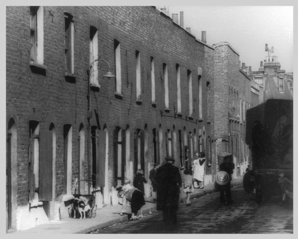 Working class people outside their slum terraces, London