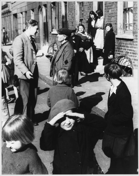 A lively scene on a street full of children, in a Working Class area of London