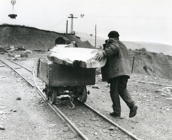 A workman pushing a slate quarry tram with a large block of slate resting on top of it, somewhere in North Wales. These small trams can carry up to half a ton of raw slate