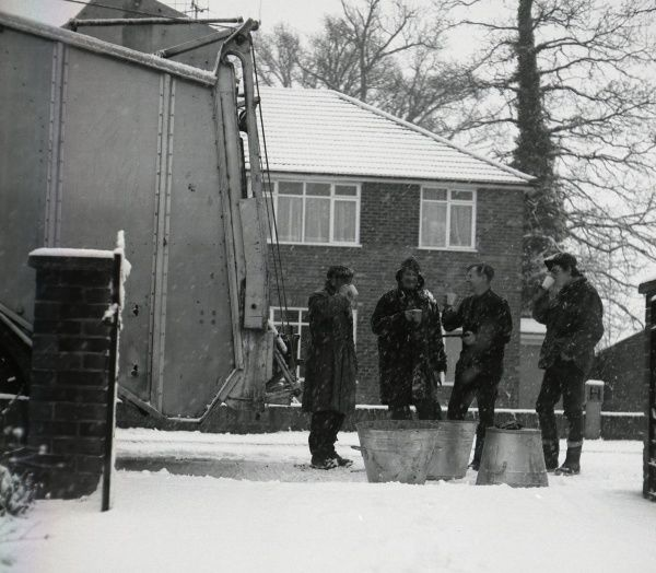 Four workmen stop for a welcome cup of tea on a snowy winter's day. (1 of 2)