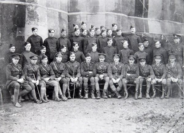 A World War One aviation group, in uniform. The officers sit on the front row, and the men stand behind