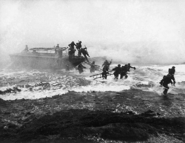 Soldiers landing from a landing craft under cover of a smoke screen during World War II in 1941