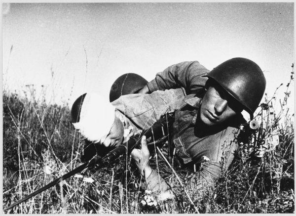A Soviet soldier brings in a wounded comrade