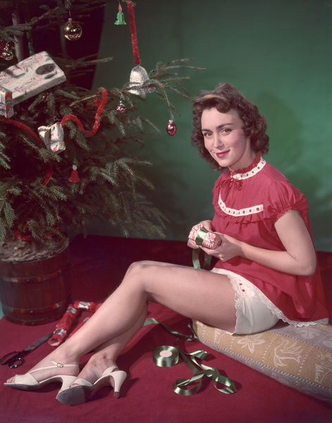 Festive model in red baby doll nightie with broderie Anglaise trim & white slingback shoes sits on a cushion & wraps presents, showing her knickers in the process