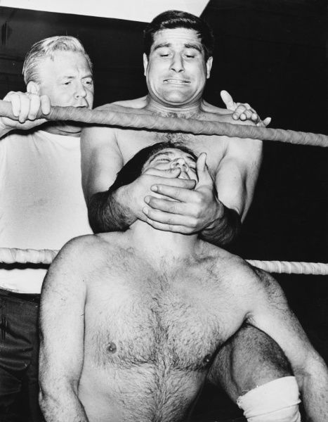 A wrestling hold under the chin and around the neck! Date: 1960s