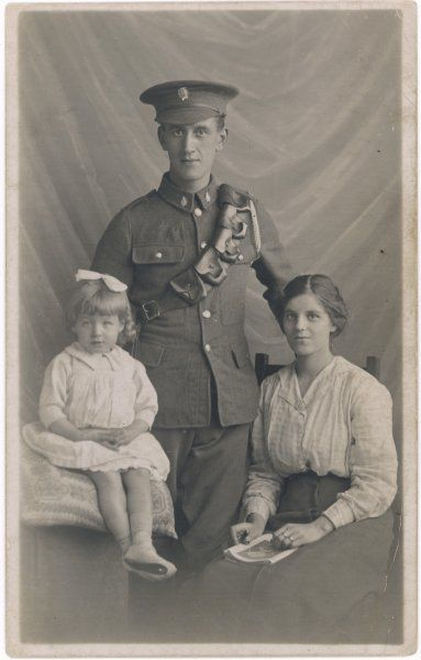 A soldier is photographed with his wife and daughter before leaving to fight for King and Country