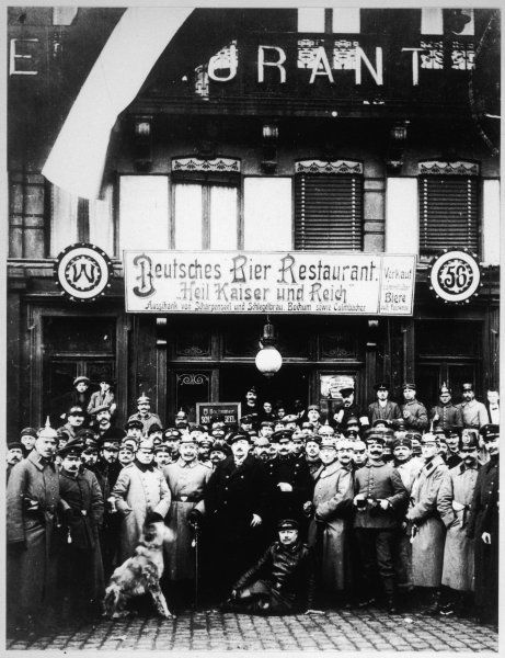 German soldiers and airmen pose for a photograph outside a Lille (?) cafe. The sign reads 'German Beer Restaurant. Heil the Kaiser and the Reich&#39